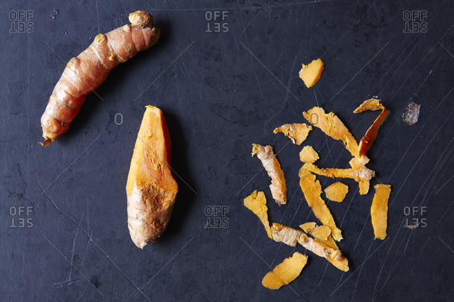 Turmeric pieces and peelings on gray background