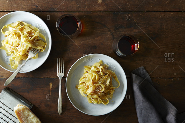 Braised onion pasta on two plates with wine