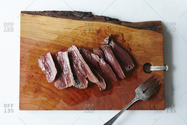 Cooked beef heart slices on cutting board
