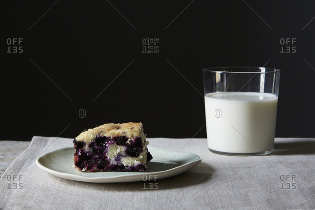 Piece of blueberry cake and glass of milk