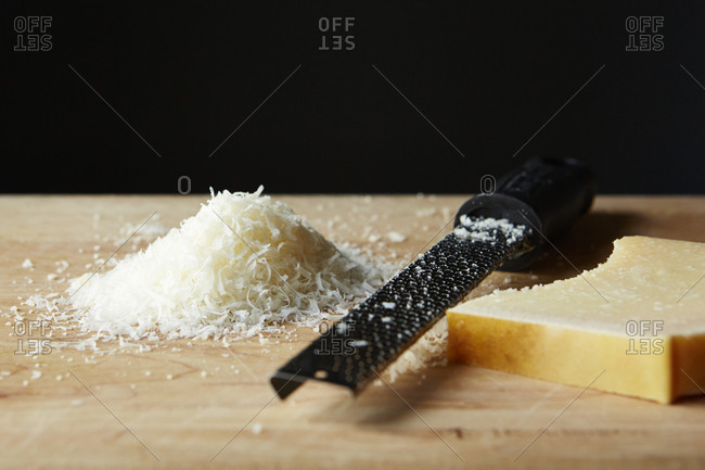 Pile of grated parmesan and grater