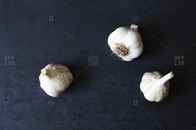 Three whole garlic heads on gray background