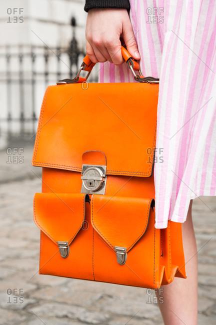 Close up of woman holding an orange handbag