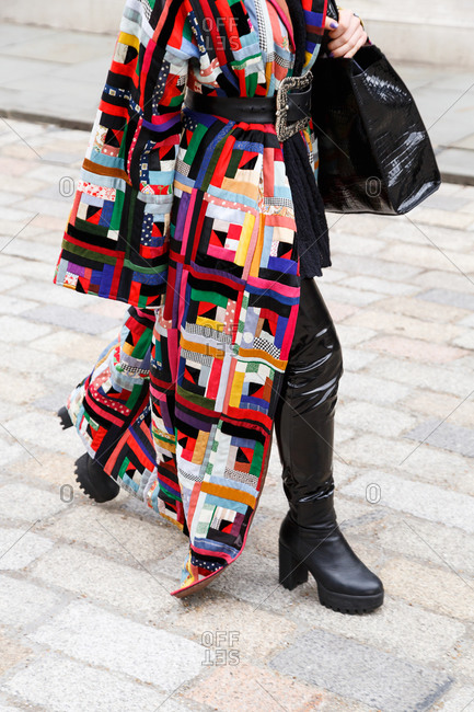 Woman walking down the street in a patchwork coat