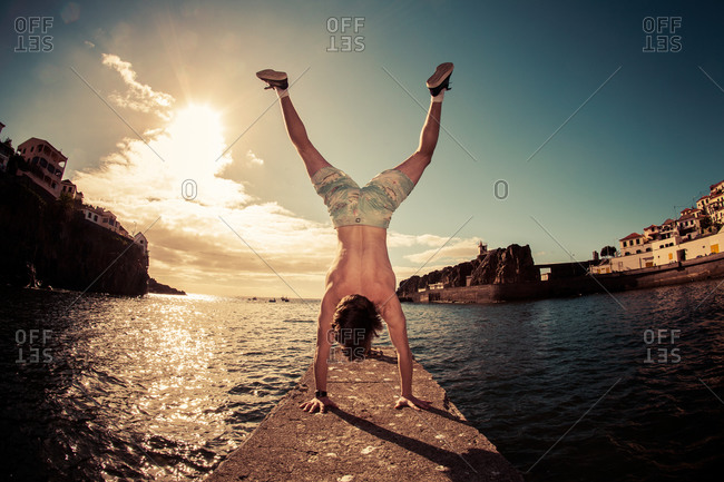 Man doing a handstand by the water
