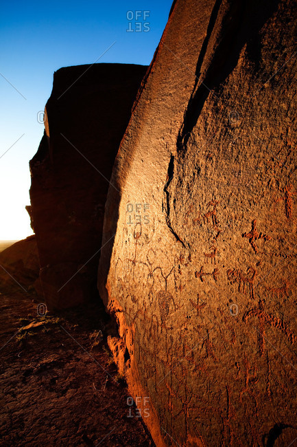 An Ancestral Puebloan (Anasazi) petroglyph panel is bathed in the warm light of the setting sun, Comb Ridge, Utah