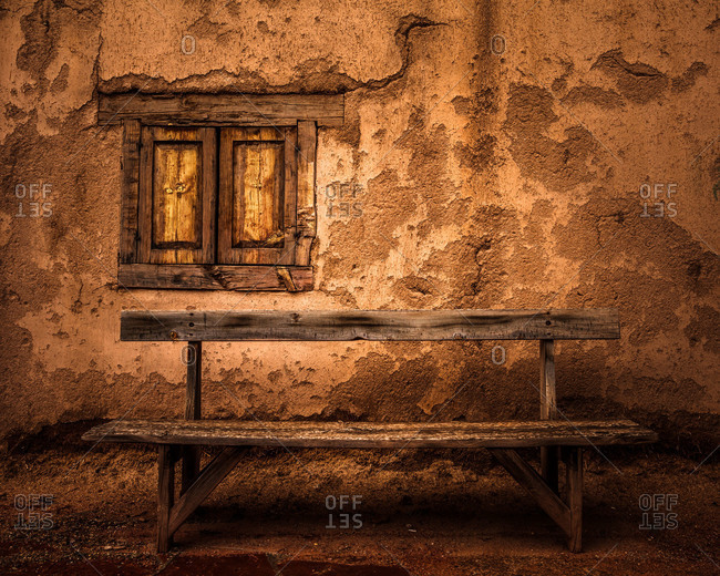 An old wooden bench in front of an adobe wall in Taos, New Mexico, USA