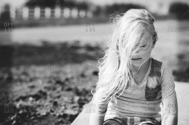 Portrait of wind blown on pensive girl in yard