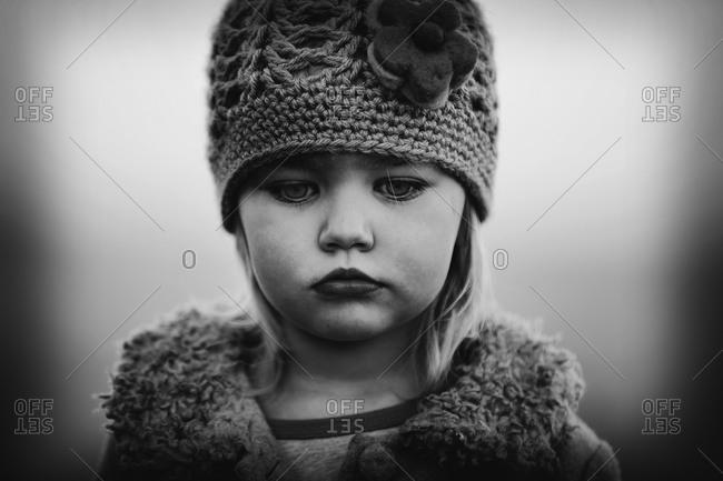 Portrait of little girl in winter hat looking down