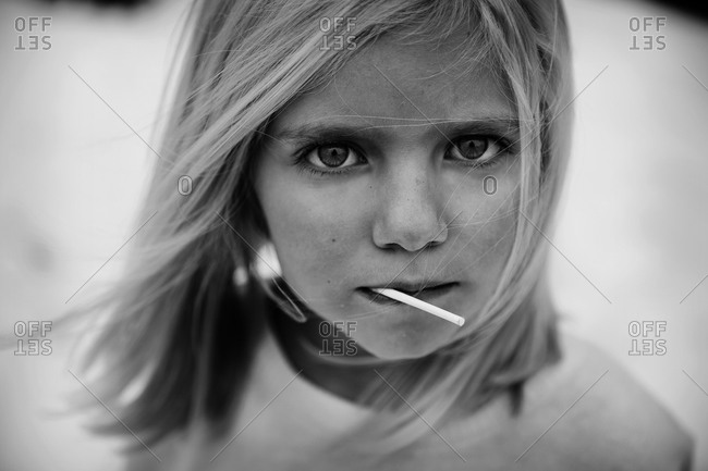 Portrait of girl eating sucker in black and white