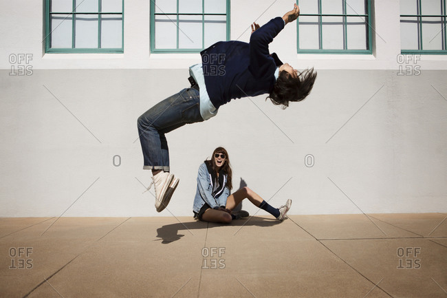 Young man doing a backflip in front of his friend