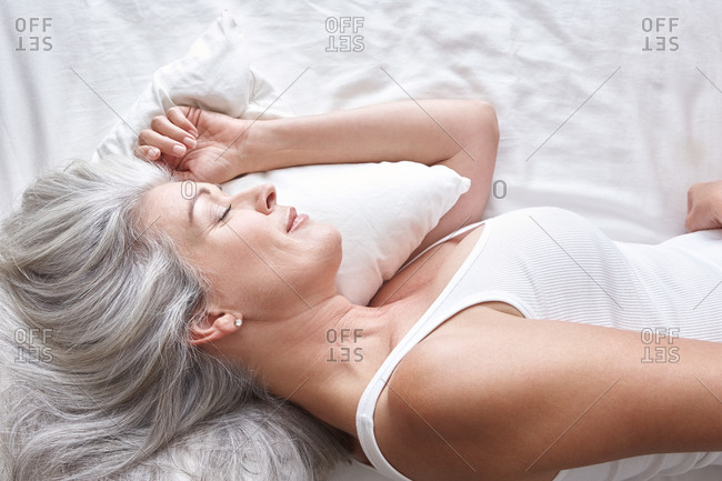 Woman with grey hair sleeping in bed