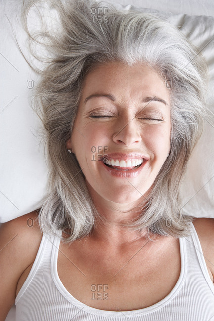Woman with grey hair lying in bed laughing