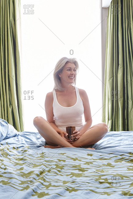 Woman with grey hair sitting on bed in bedroom with coffee cup