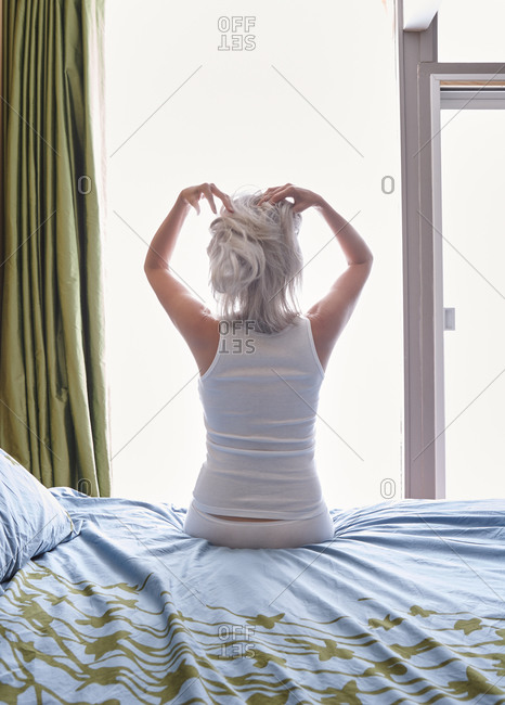 Woman with grey hair sitting on edge of bed in bedroom