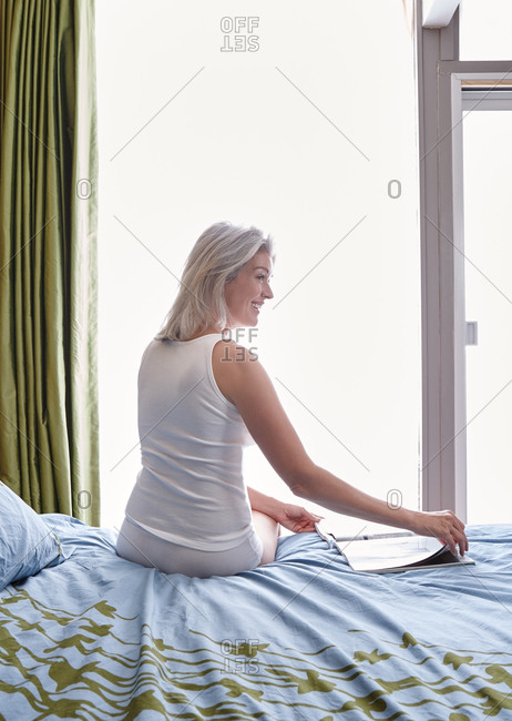 Woman with grey hair sitting on bed in bedroom reading a magazine