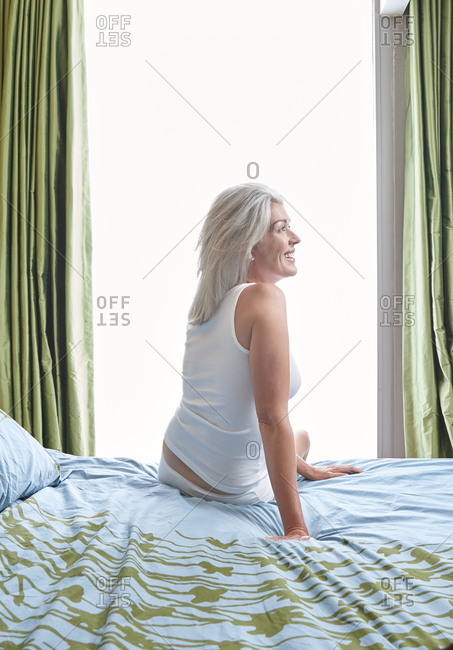 Woman with grey hair sitting on bed smiling