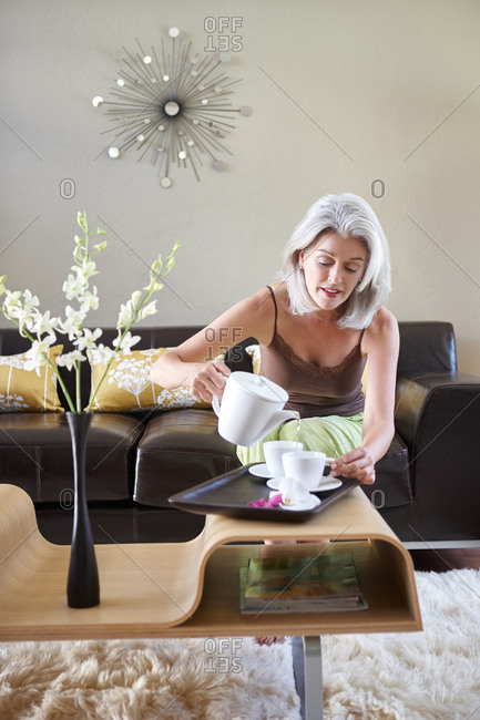 Woman with grey hair with tea set in living room