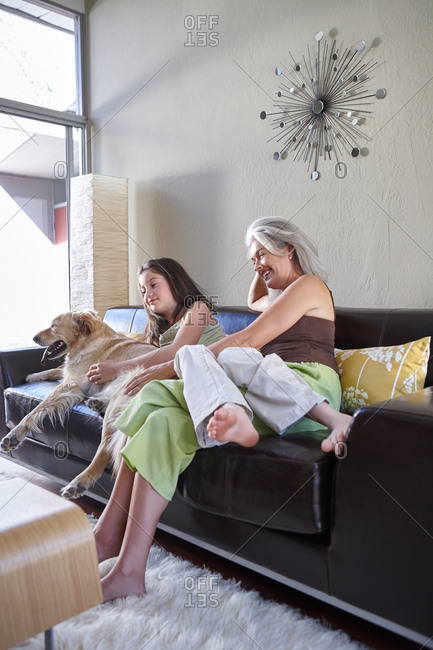 Mother and daughter in living room with dog