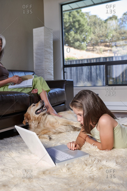 Little girl working on computer in living room with her mom and dog