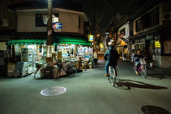 Bicyclists in Osaka street corner at night