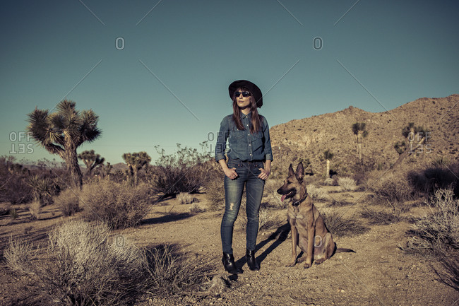 A woman and her dog look out into the desert