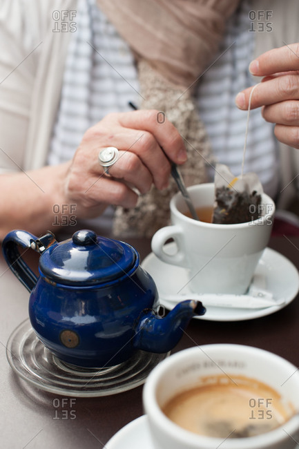 Woman prepares a cup of tea at cafe