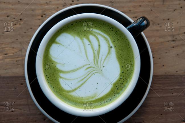A matcha tea latte with a flower design