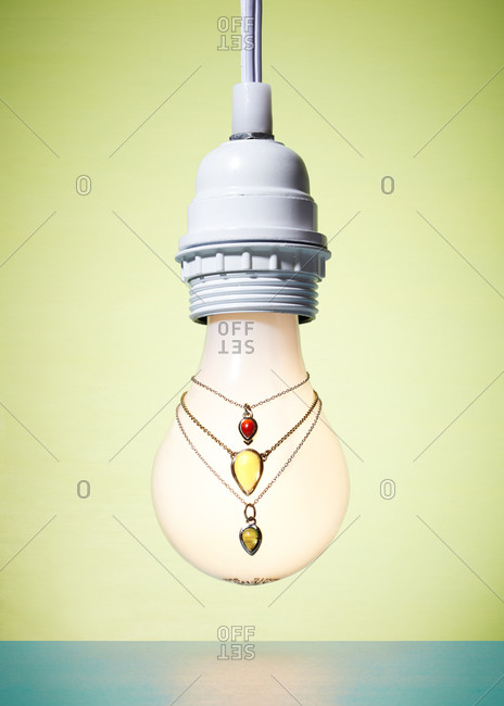 Three gemstone necklaces hanging on a light bulb