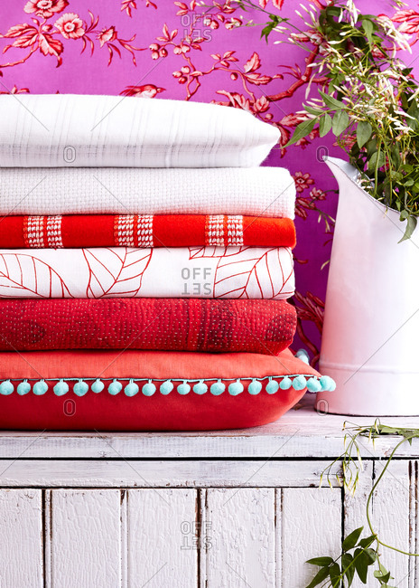 Stack of red and white linens and pillows