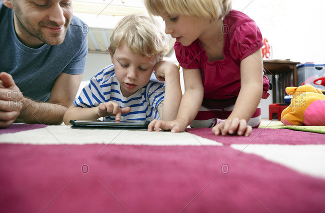 Father and children using mini tablet, lying on floor