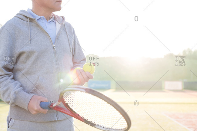 Tennis player with tennis balls and racket at backlight