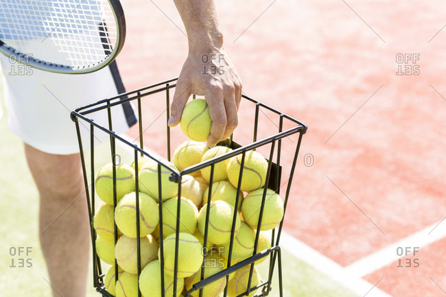 Man\'s hand taking tennis ball out of wire basket