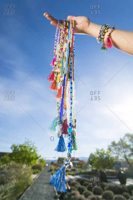 Woman holding up beaded necklaces