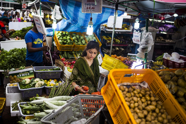 Little India, Singapore - March 8, 2015: A woman shops for produce at a market stall in Little India, Singapore