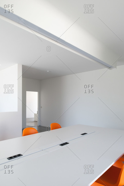 Two orange chairs in front of a mirror in a white room