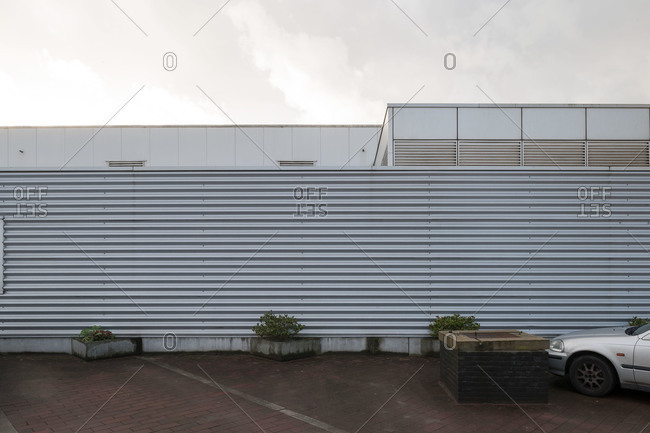 Corrugated steel wall running along parking area of a commercial building
