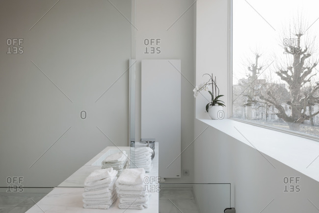 Clean, white modern bathroom counter with folded towels