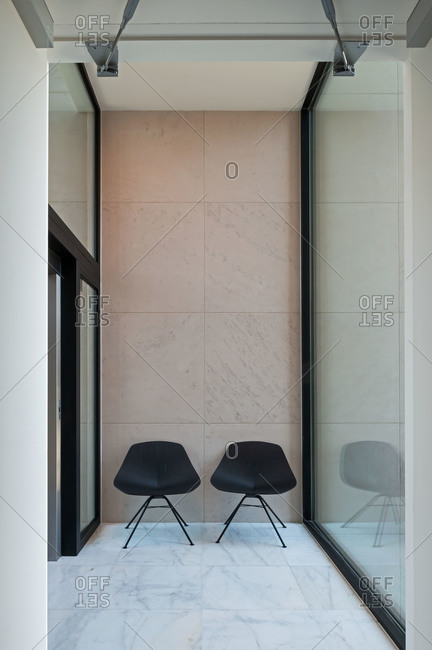 Entryway of office building with two black chairs