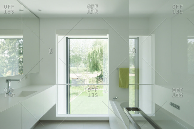 Modern white bathroom with long counter leading to window