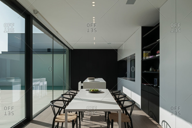 Long dining table in a modern white and black kitchen
