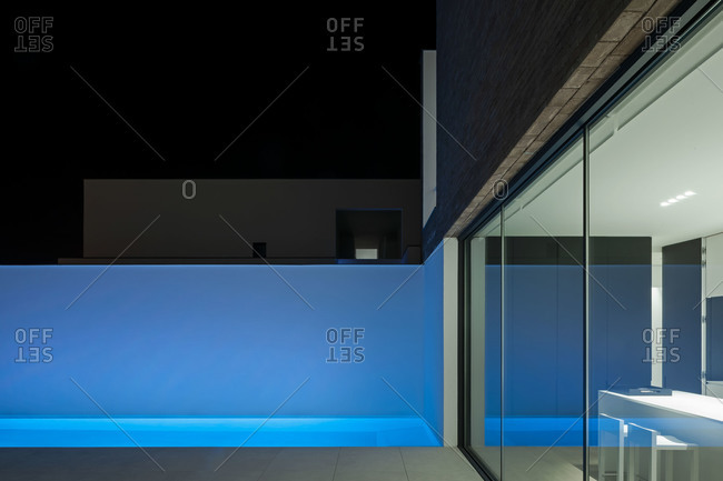Swimming pool casts a blue glow against white stucco wall at night