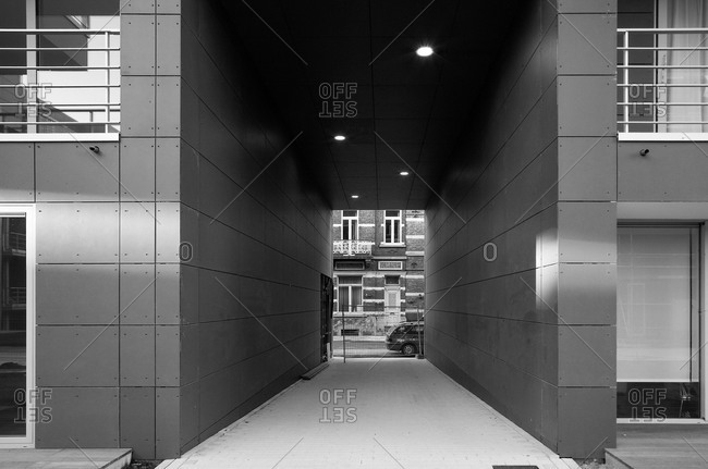 Looking through a tunnel to the street from a courtyard of a modern building