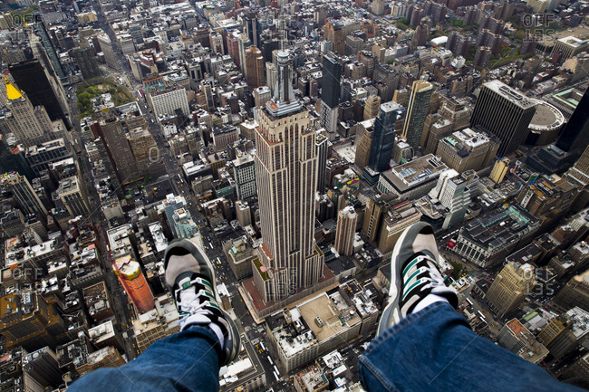 May 3, 2014: Person dangling his legs above the Empire State Building, NYC