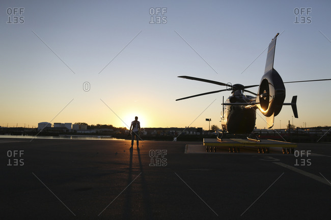 Man standing at a helicopter at sunset