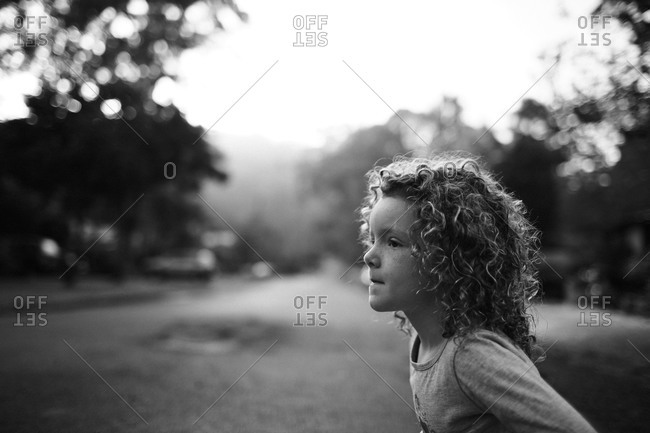 A curly haired girl stands in the middle of a street