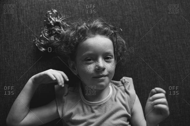 A little girl with freckles lays on the floor
