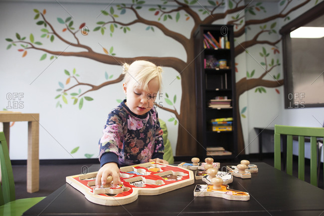 Young girl in preschool with large puzzle