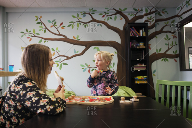 Woman teaching young girl with animal puzzle