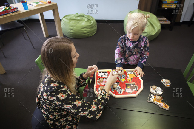 Woman helping young girl with animal puzzle